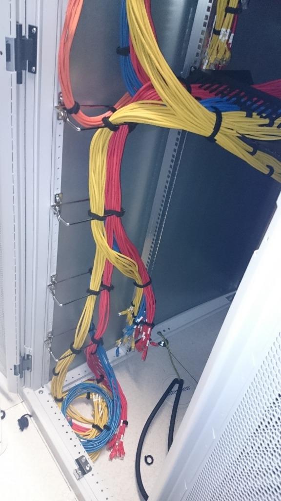 Kabels met kleurencodes vertrekken vanuit het midden van de datacenter racks